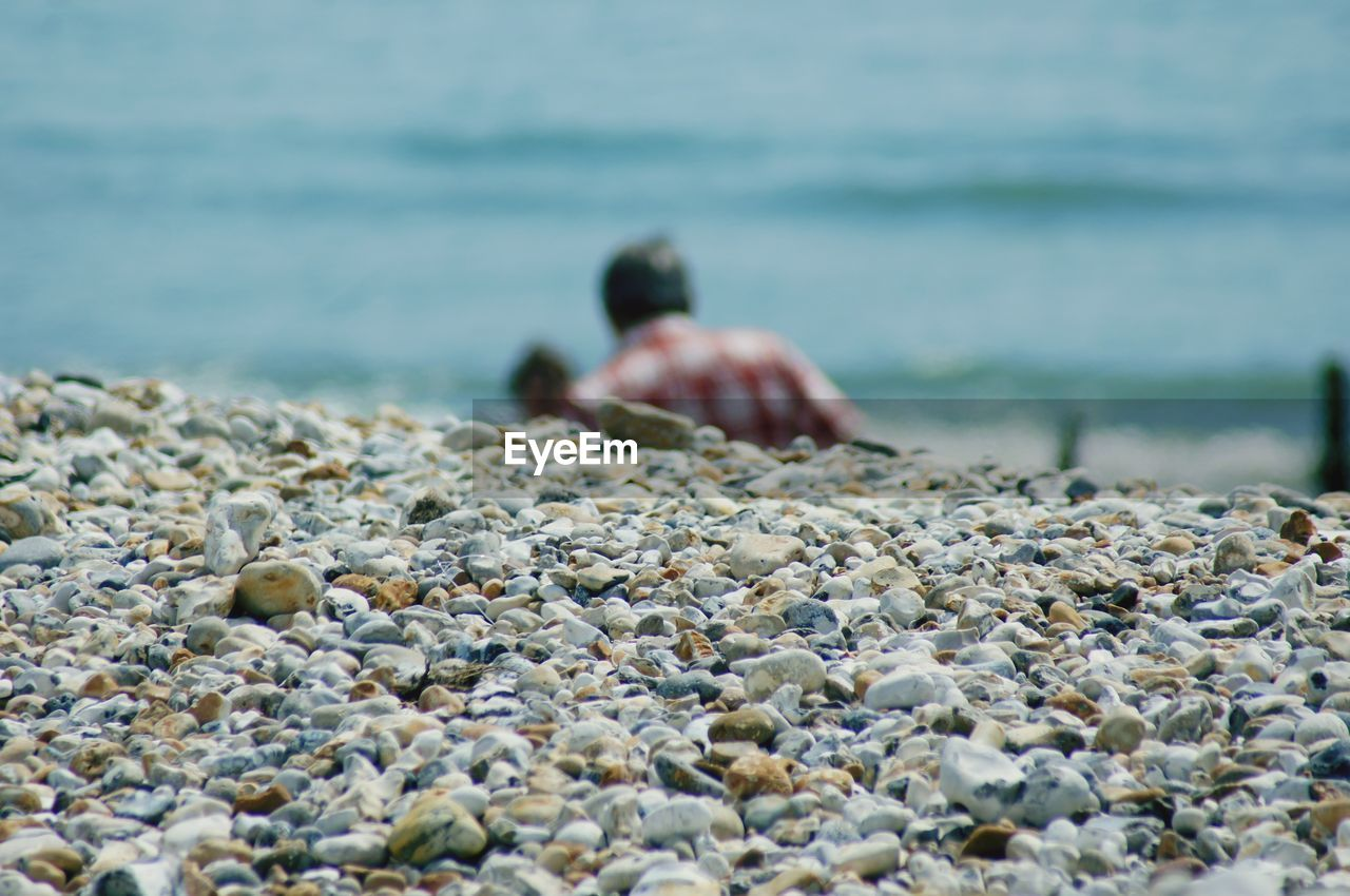 water, one person, sea, real people, selective focus, solid, rock, leisure activity, nature, lifestyles, day, beach, land, stone - object, beauty in nature, rock - object, hand, outdoors, pebble, surface level