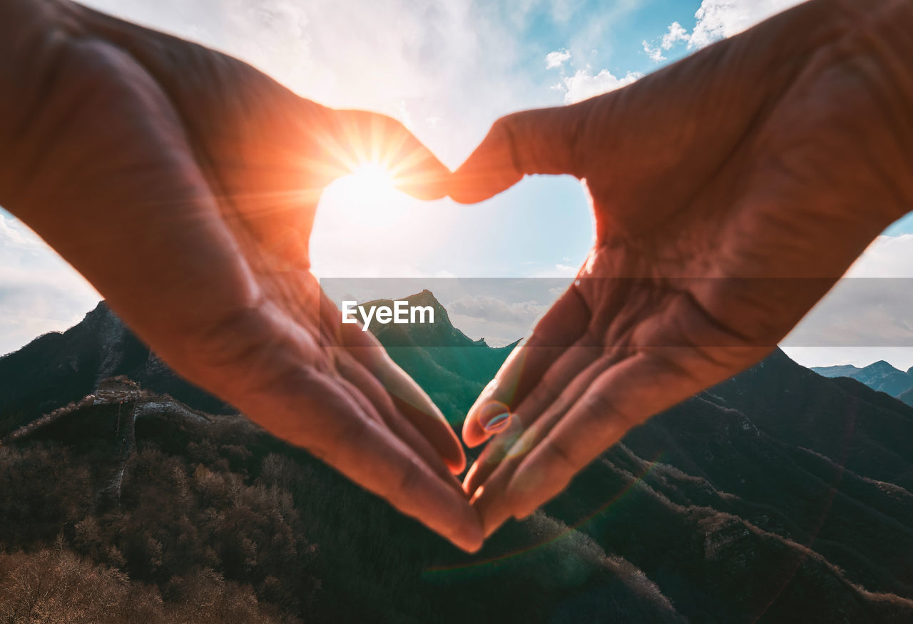Cropped hands of person making heart shape against mountains and sky