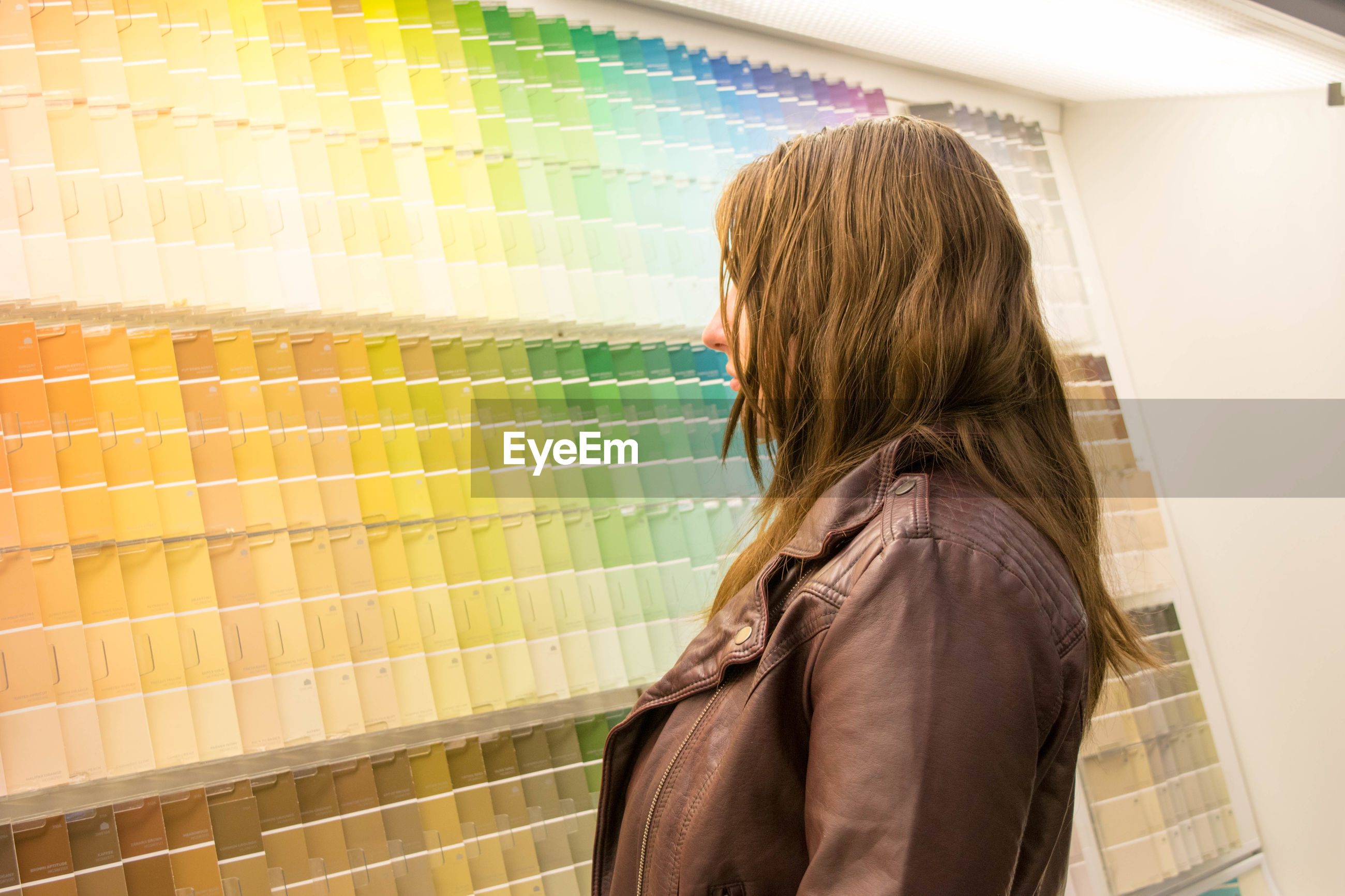 Side view of young woman standing by colorful color swatches at store