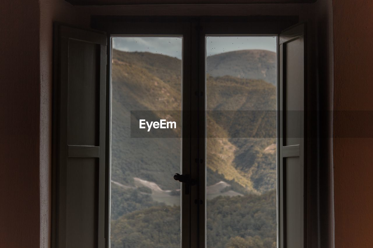 window, mountain, landscape, nature, indoors, door, scenics, curtain, day, tranquil scene, no people, beauty in nature, architecture, sky, close-up