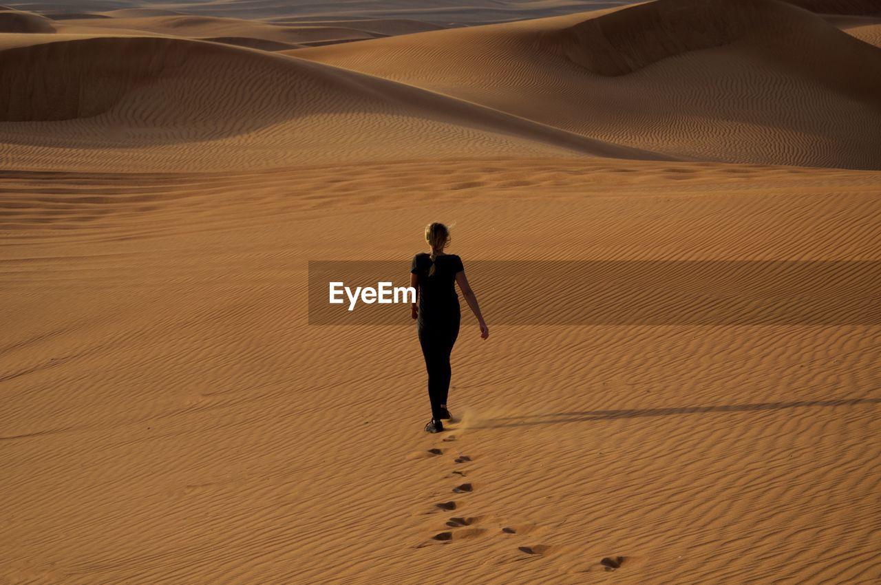 Rear view of woman walking on sand in desert