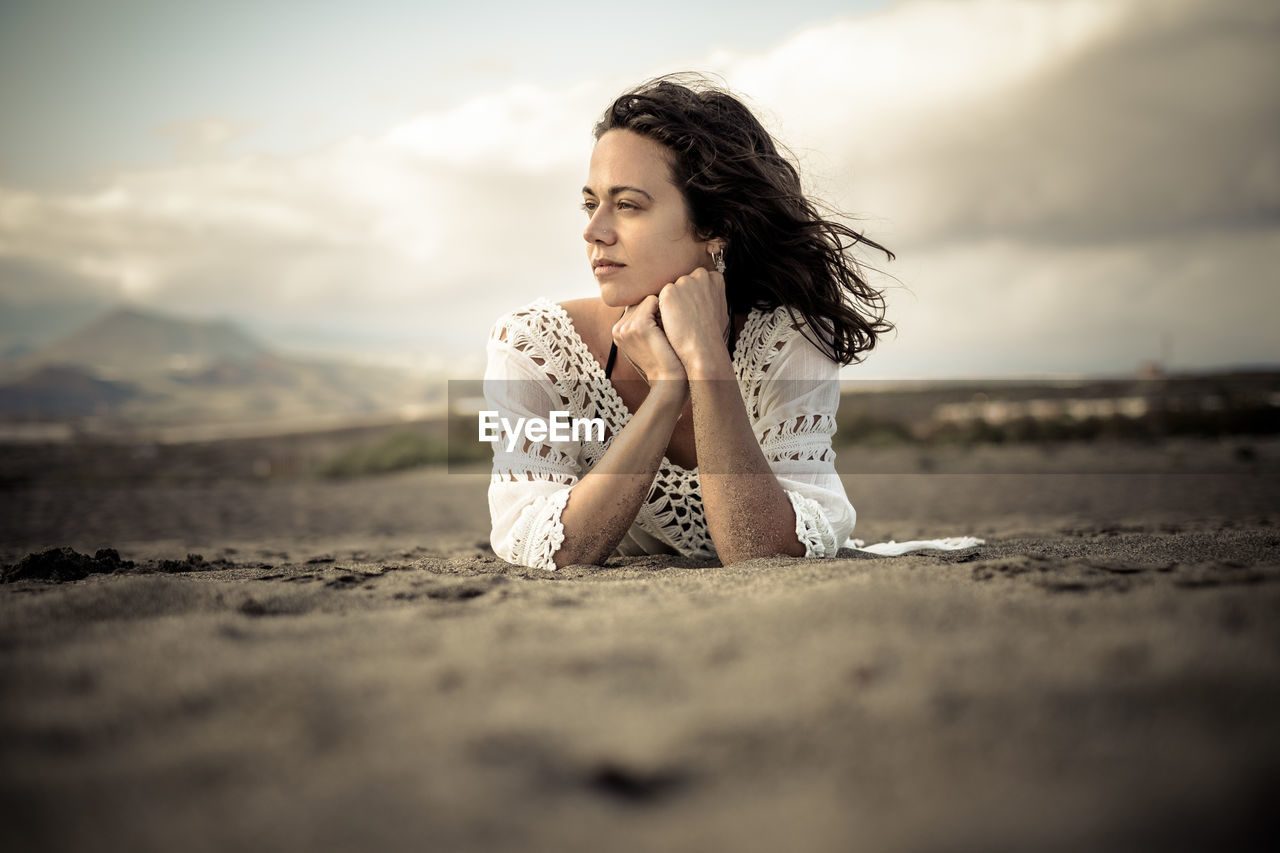 Thoughtful young woman lying on field against sky during sunset