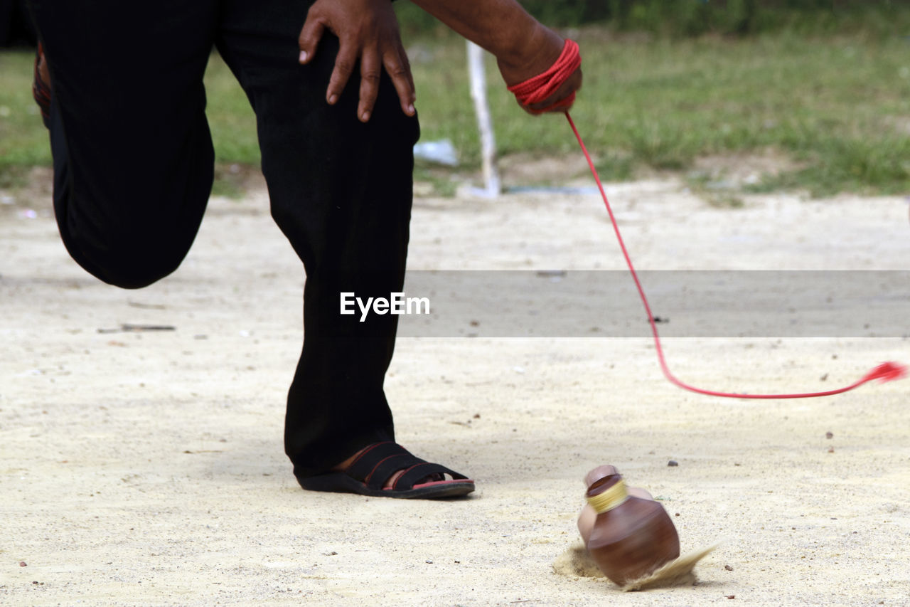 Low section of man playing with spinning top