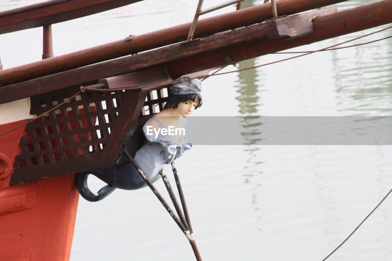 nautical vessel, one person, rope, day, real people, mode of transport, water, transportation, outdoors, occupation, headwear, helmet, sailing, nature, young adult, people