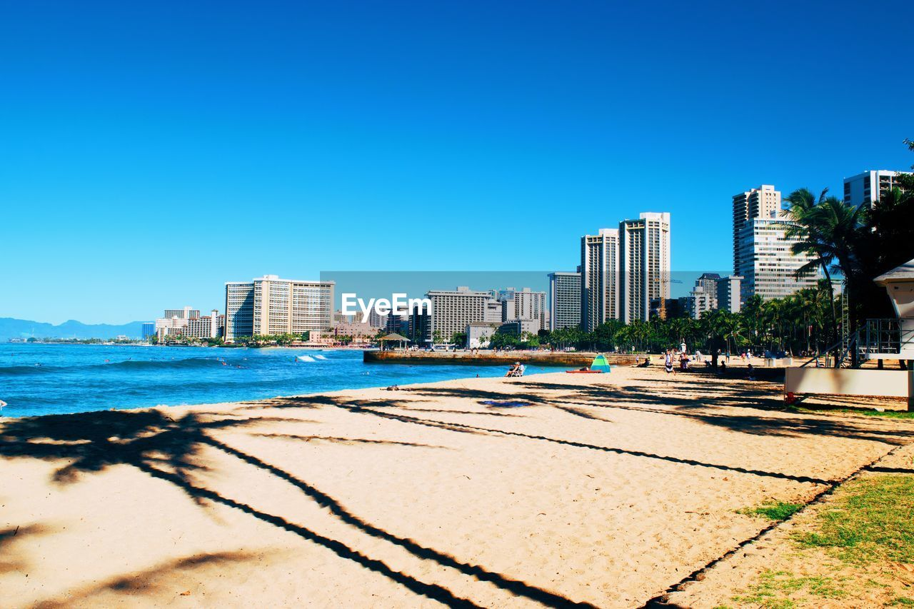 sky, building exterior, built structure, architecture, city, clear sky, water, beach, blue, nature, land, sunlight, building, copy space, sea, day, sand, no people, urban skyline, outdoors, office building exterior, skyscraper, cityscape