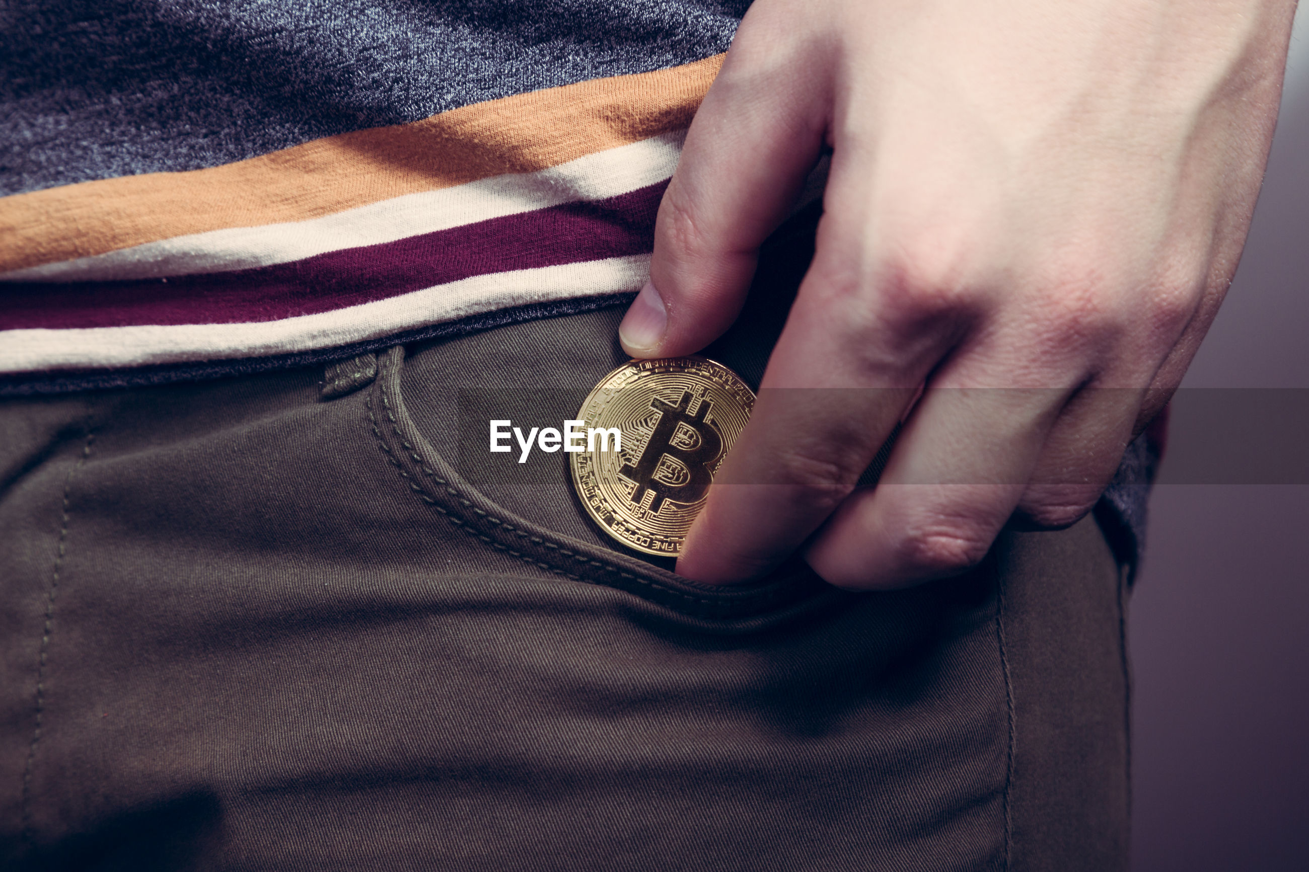 Midsection of person putting bitcoin in pocket
