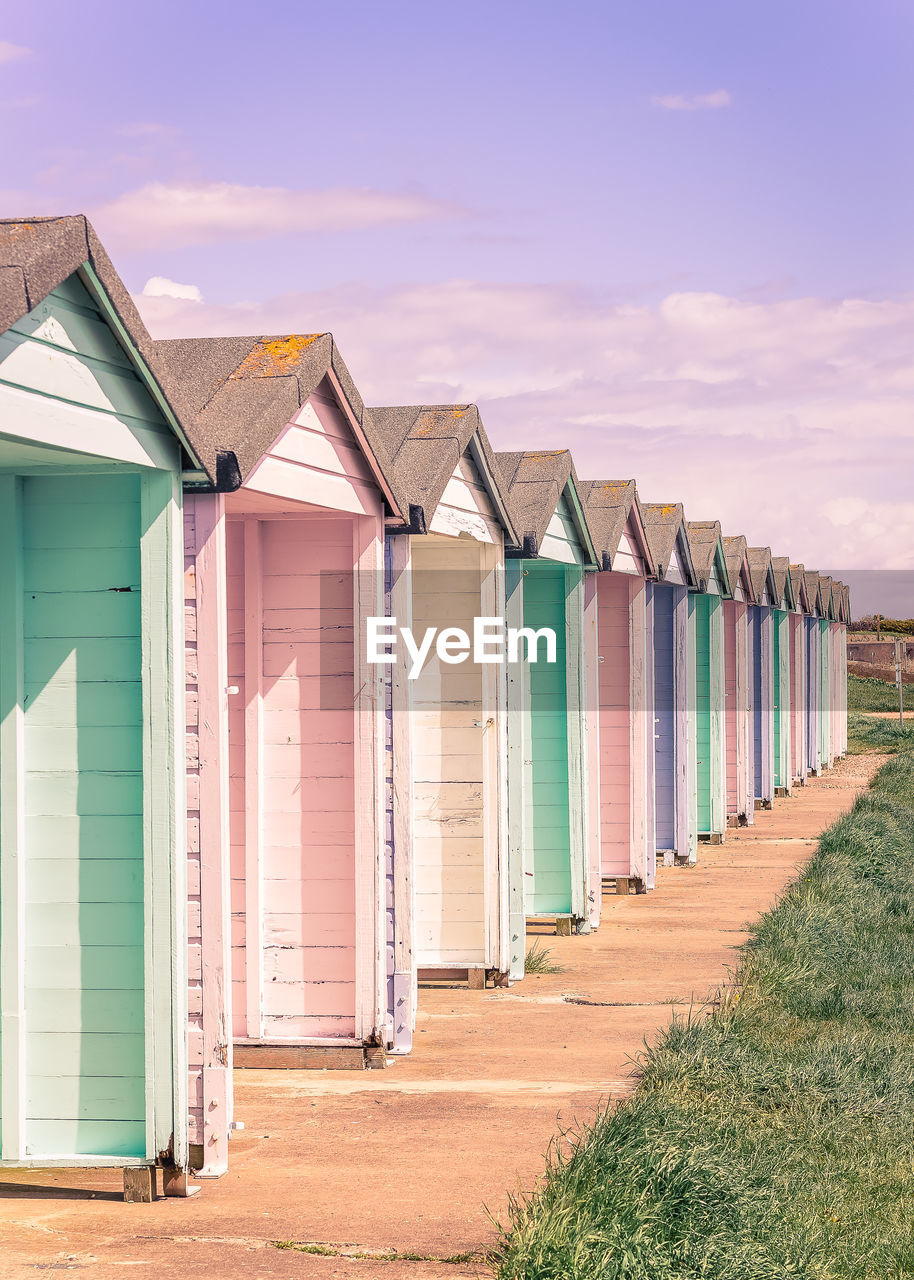 beach hut, built structure, architecture, in a row, hut, multi colored, land, sky, building exterior, beach, side by side, nature, day, no people, cloud - sky, outdoors, building, sand, house, repetition, cabin