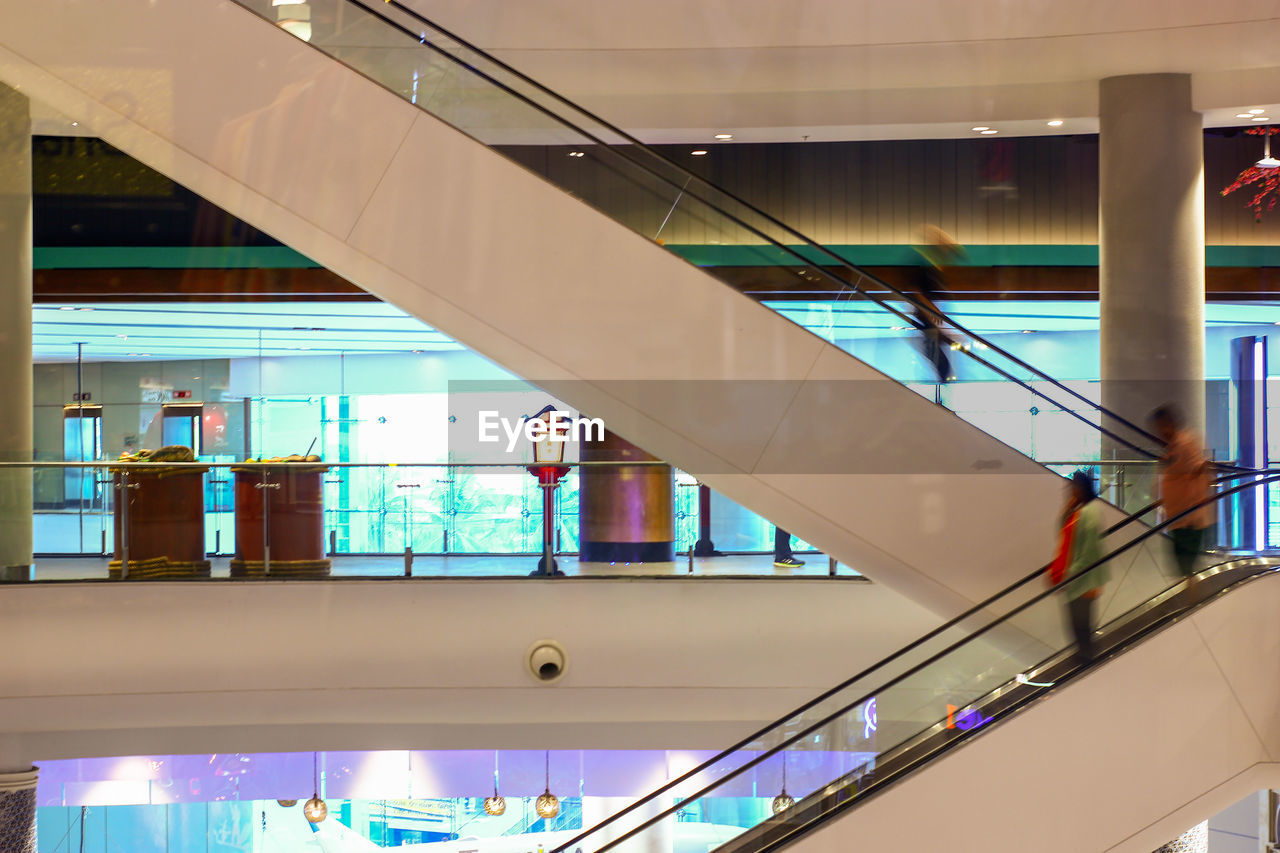 architecture, built structure, railing, building exterior, glass - material, modern, illuminated, day, incidental people, building, staircase, outdoors, shopping mall, transparent, real people, window, escalator, convenience, ceiling, moving walkway