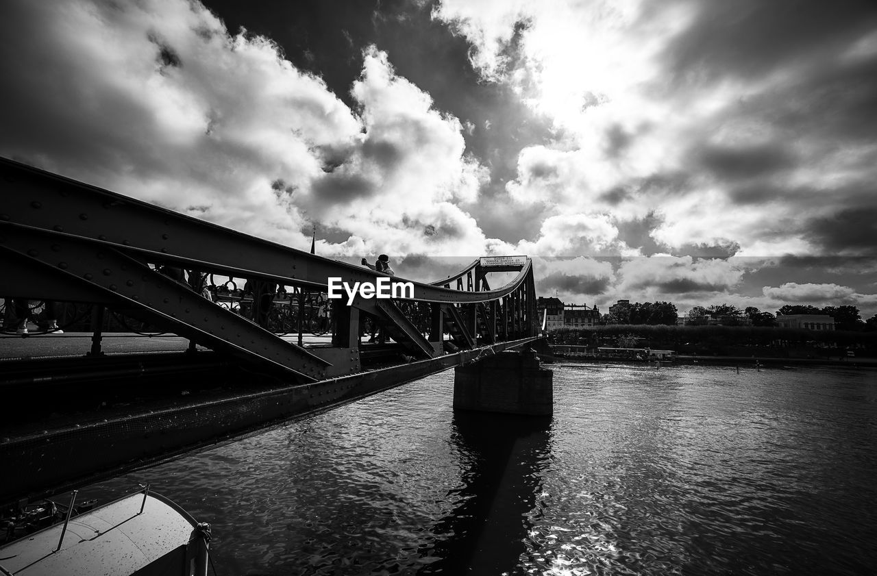 water, bridge, built structure, architecture, cloud - sky, bridge - man made structure, sky, connection, river, transportation, waterfront, nature, engineering, day, building exterior, outdoors, city, travel destinations, long