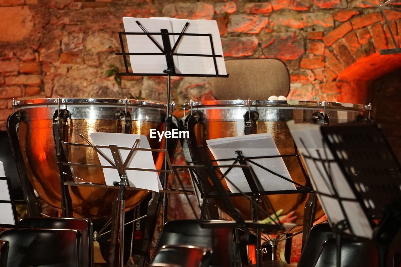 Close-up of drums and music sheets against brick wall