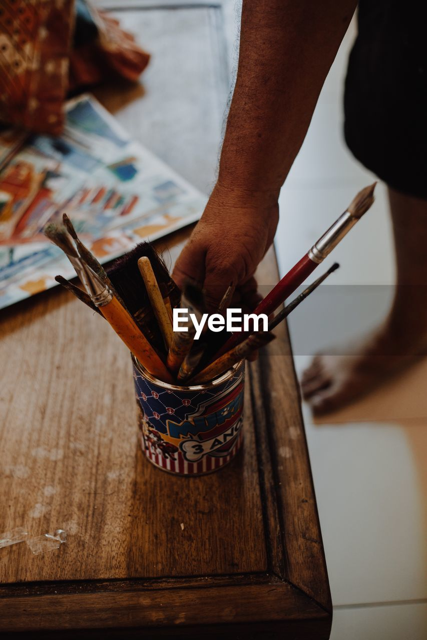 human hand, hand, one person, human body part, real people, indoors, holding, wood - material, men, focus on foreground, unrecognizable person, occupation, close-up, table, skill, paintbrush, working, lifestyles, body part, finger