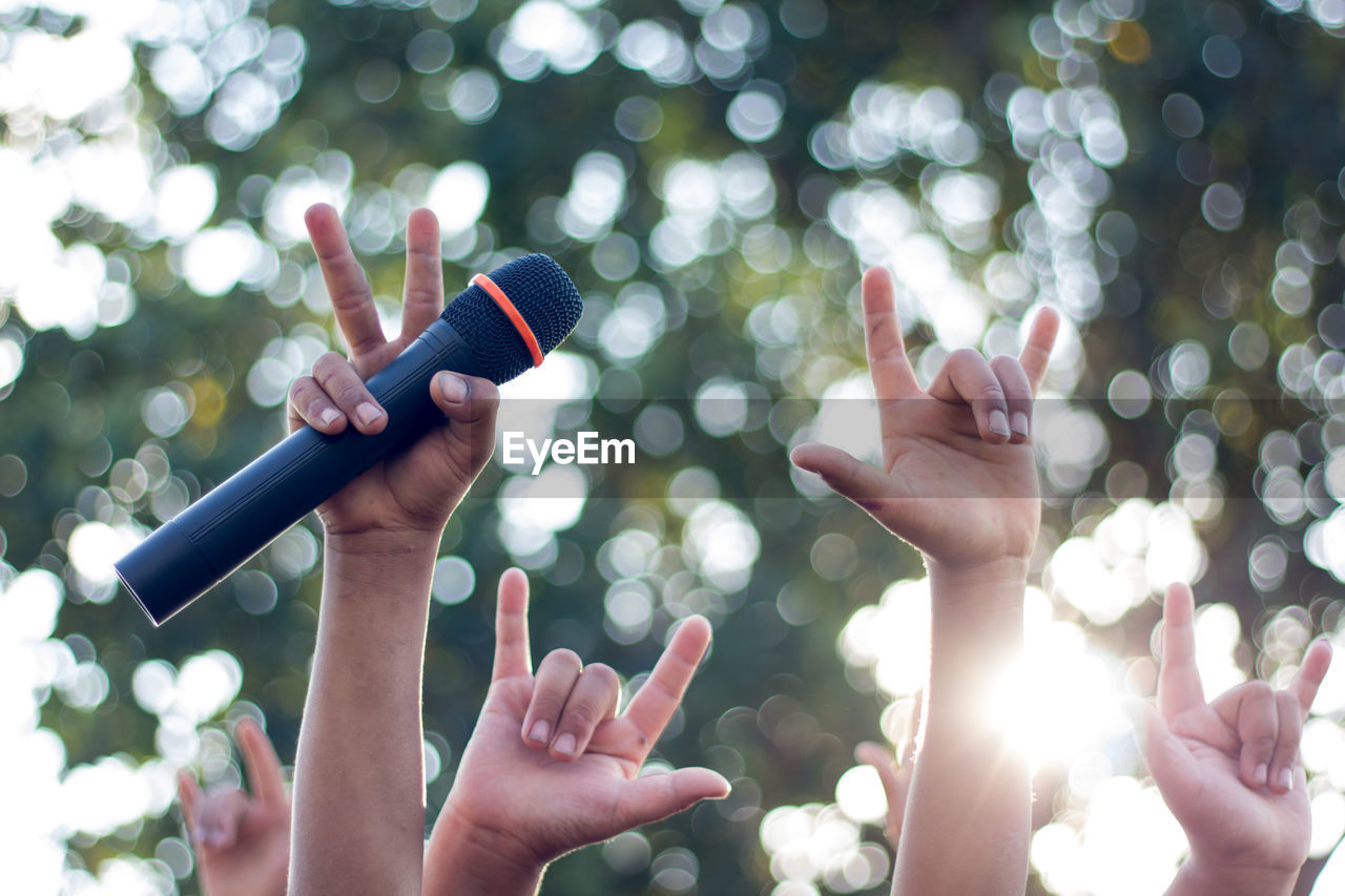 Cropped hand of person holding microphone against trees