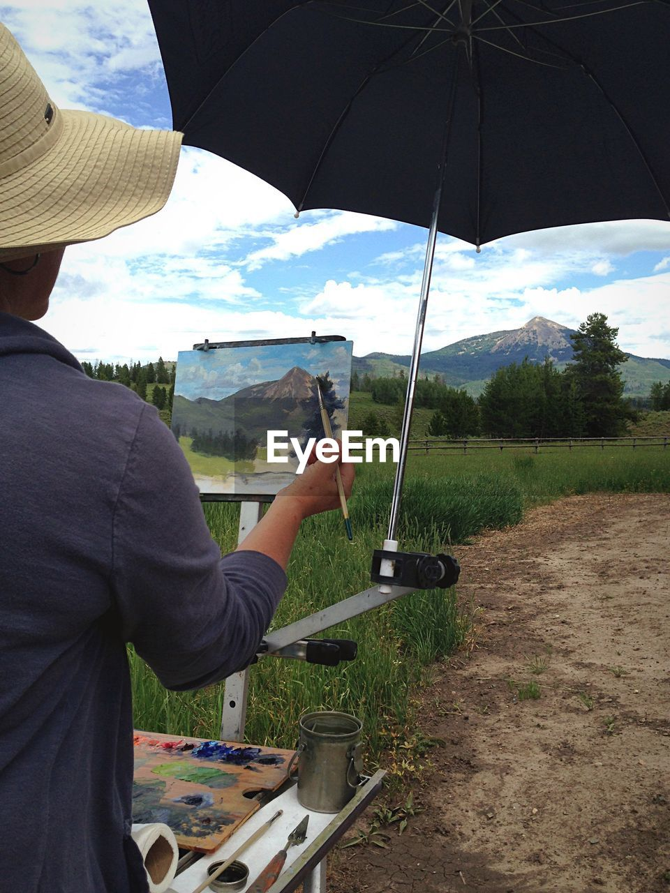 Rear View Of Woman Painting Landscape