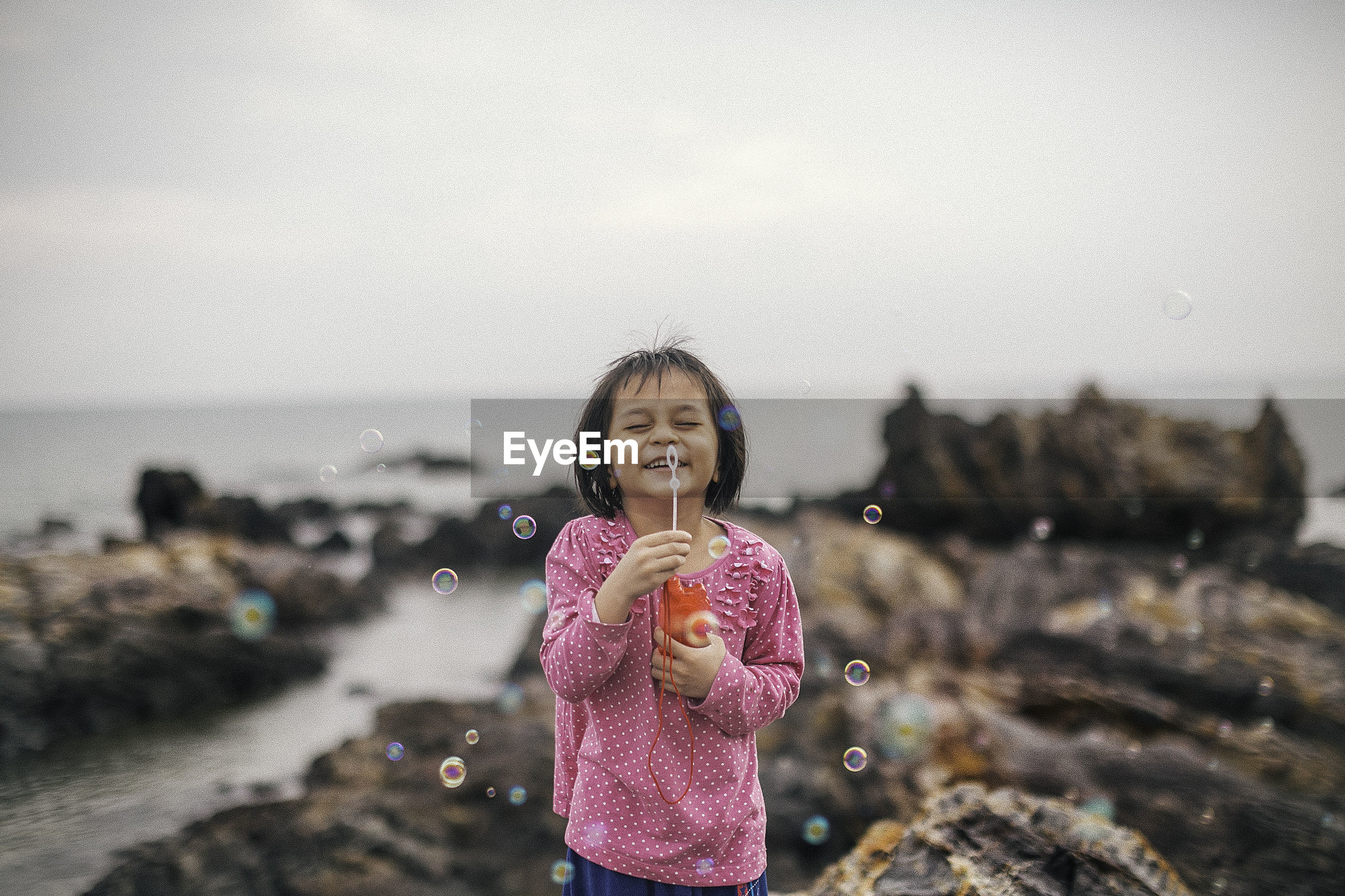 Portrait of girl holding bubble wand  against sky