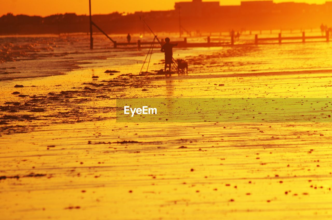 water, sunset, silhouette, sea, land, real people, beach, beauty in nature, nature, sky, sand, one person, outdoors, orange color, men, lifestyles, nautical vessel, transportation, scenics - nature