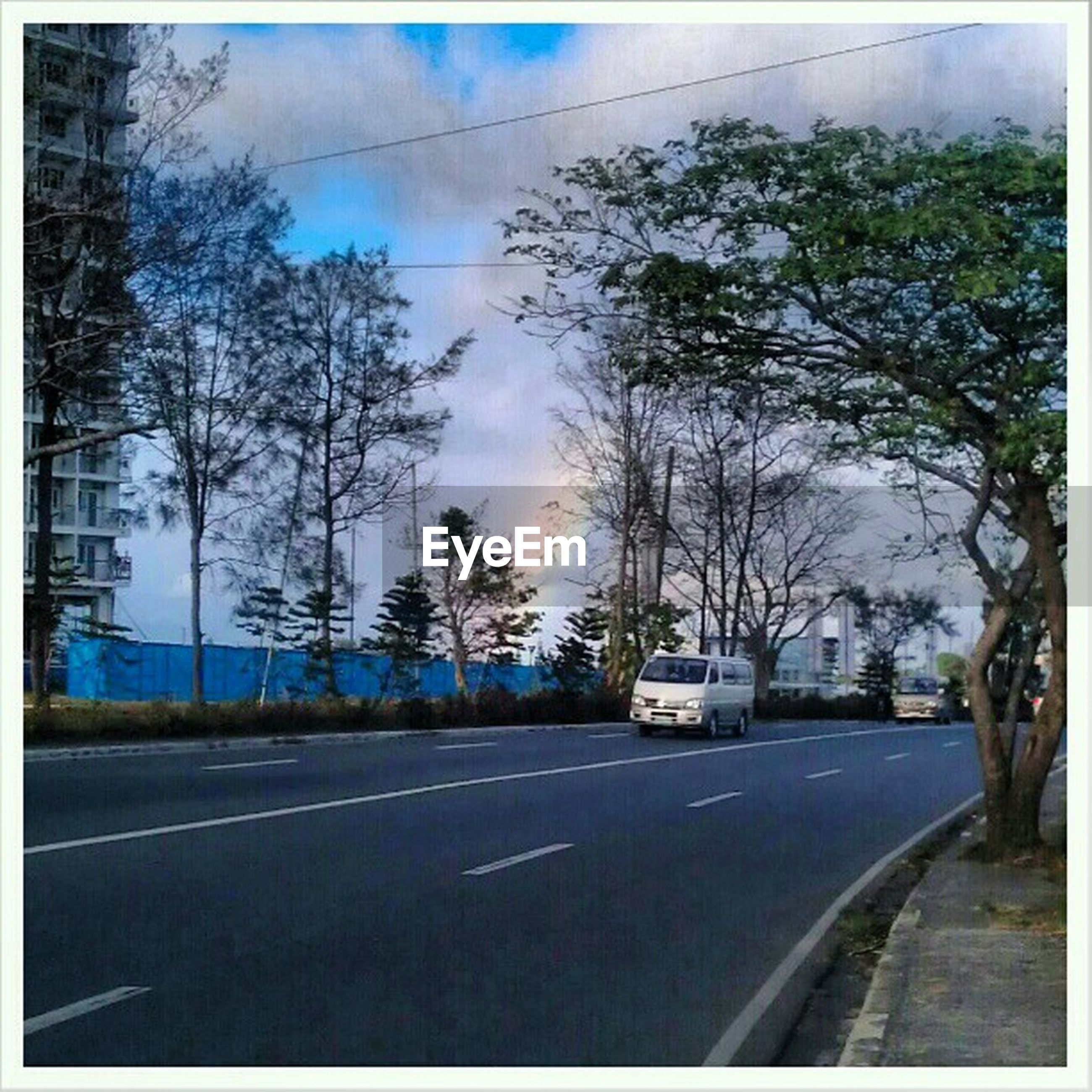 transportation, road, road marking, the way forward, tree, transfer print, sky, car, street, land vehicle, diminishing perspective, auto post production filter, mode of transport, cloud - sky, vanishing point, cloud, country road, empty, empty road, no people