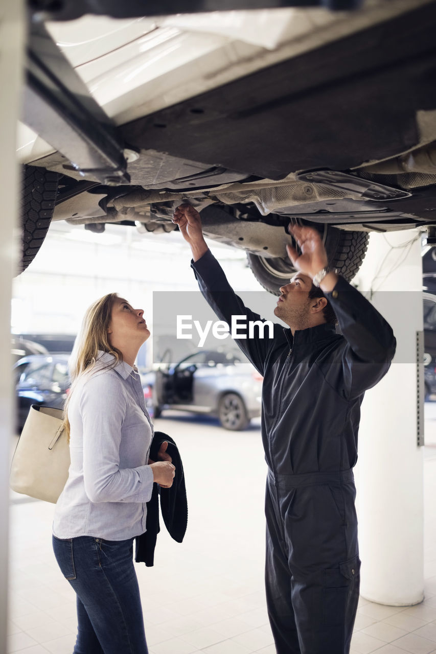 mode of transportation, men, real people, transportation, standing, occupation, adult, working, human arm, three quarter length, indoors, people, arms raised, holding, motor vehicle, two people, car, casual clothing, young adult, hand, body part, human limb, mechanic