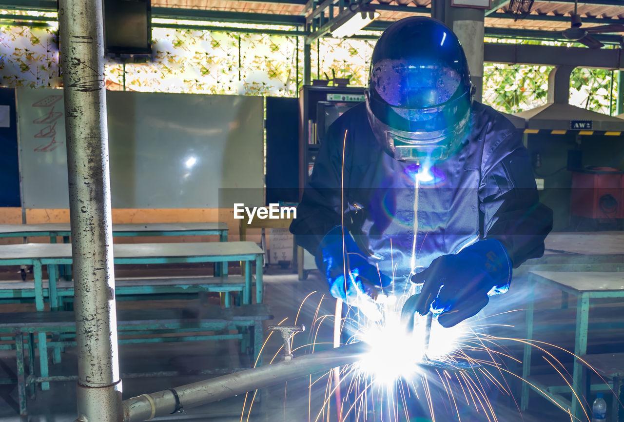 Man welding metal in factory