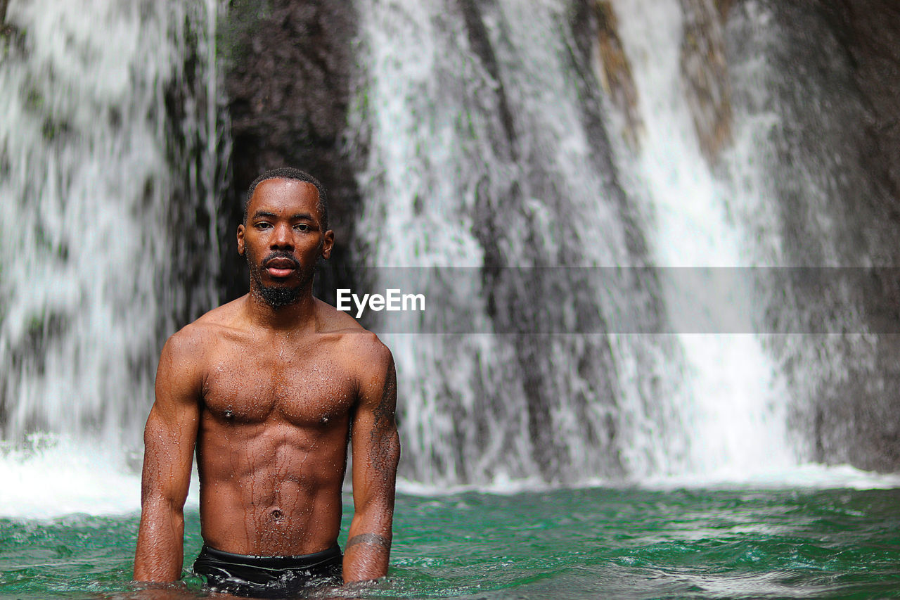 shirtless, one person, young adult, lifestyles, portrait, water, men, standing, day, real people, males, young men, leisure activity, front view, waterfall, looking at camera, muscular build, outdoors, flowing water