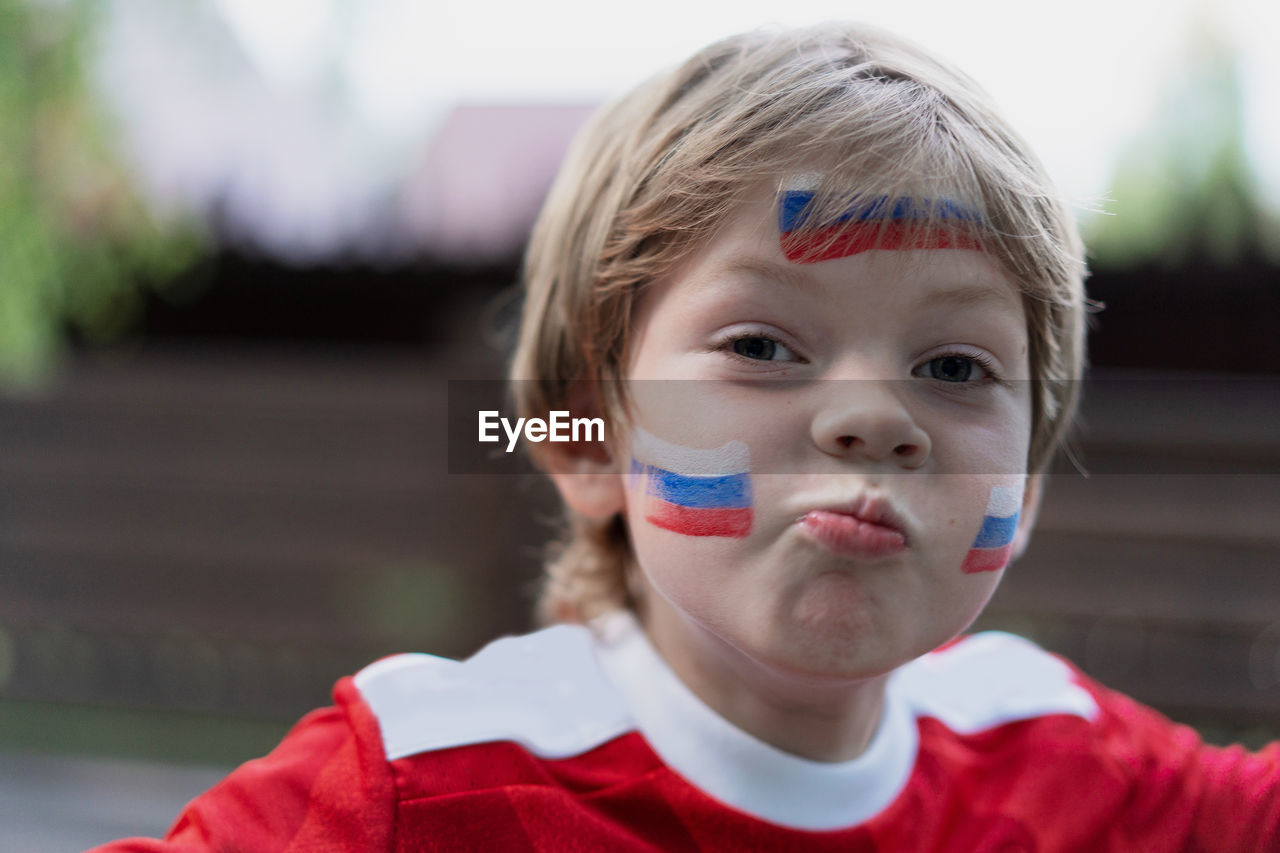 Little boy football fan with makeup on his face in the form of the russian flag.