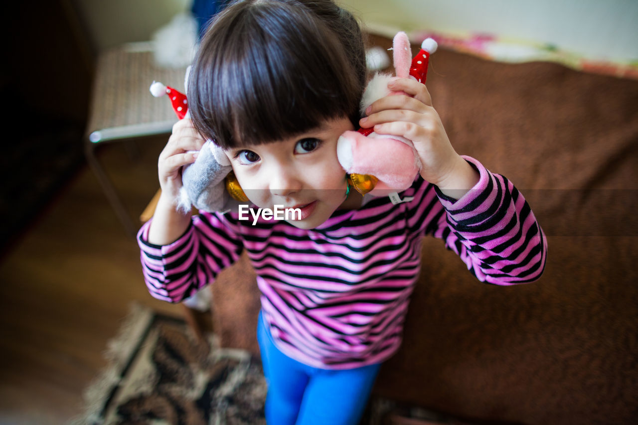 Portrait of cute girl holding toy at home