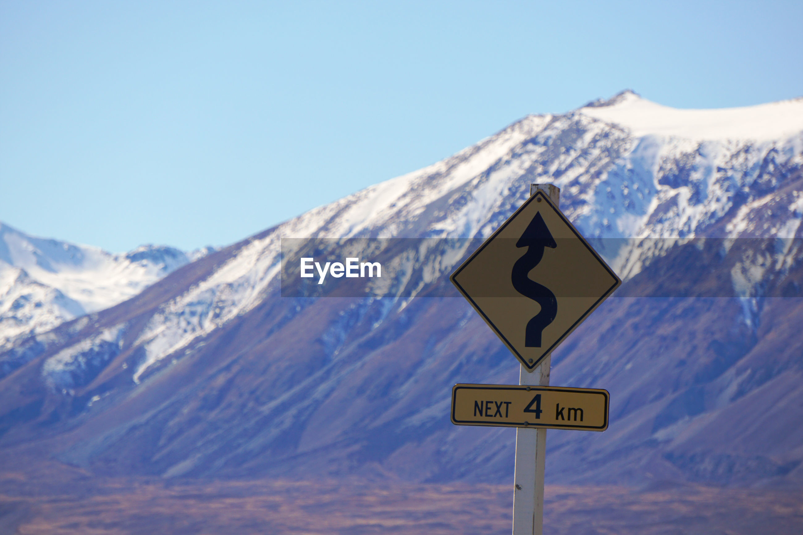ROAD SIGN BY SNOWCAPPED MOUNTAIN AGAINST SKY