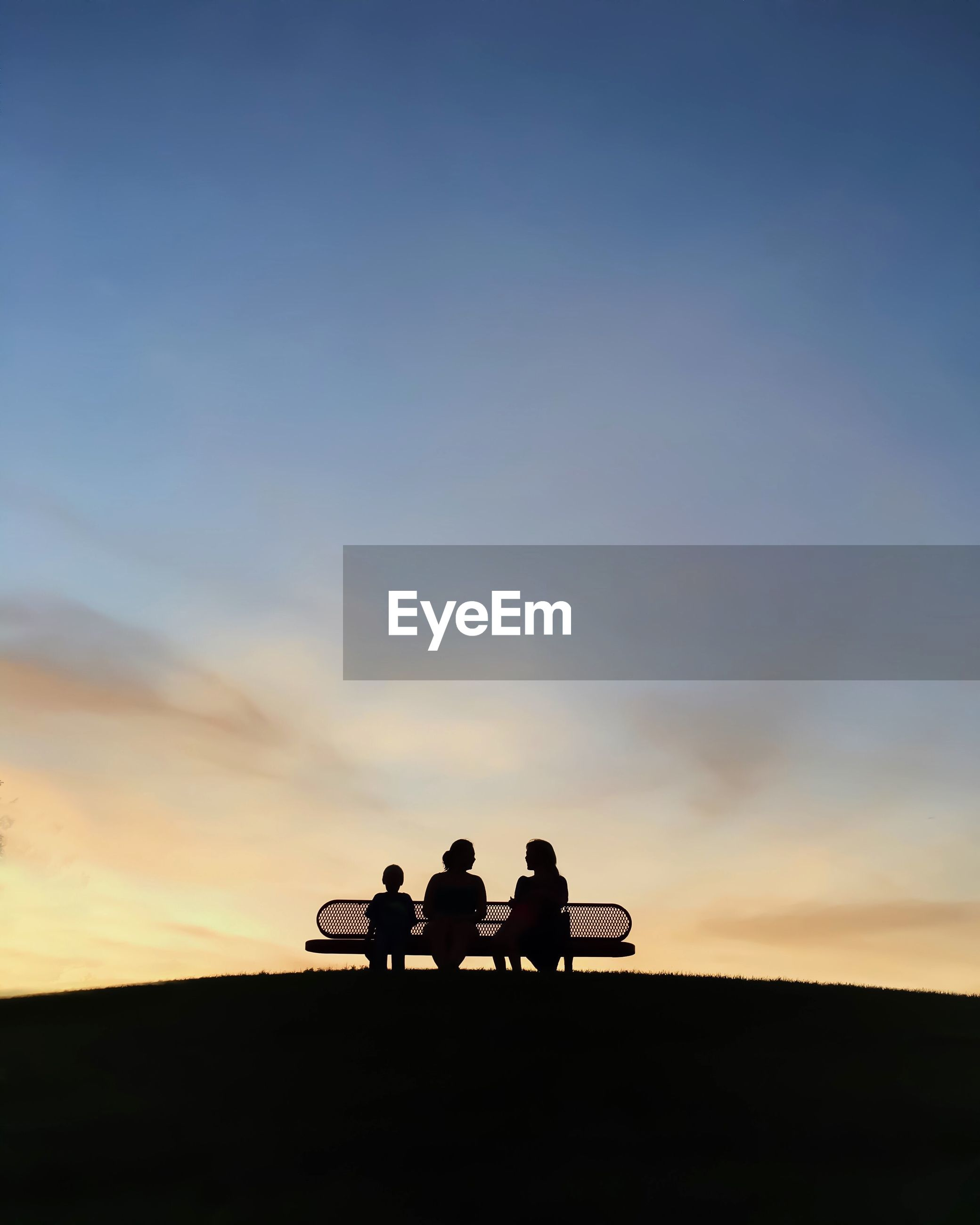 Silhouette people sitting on bench in park against sunset sky