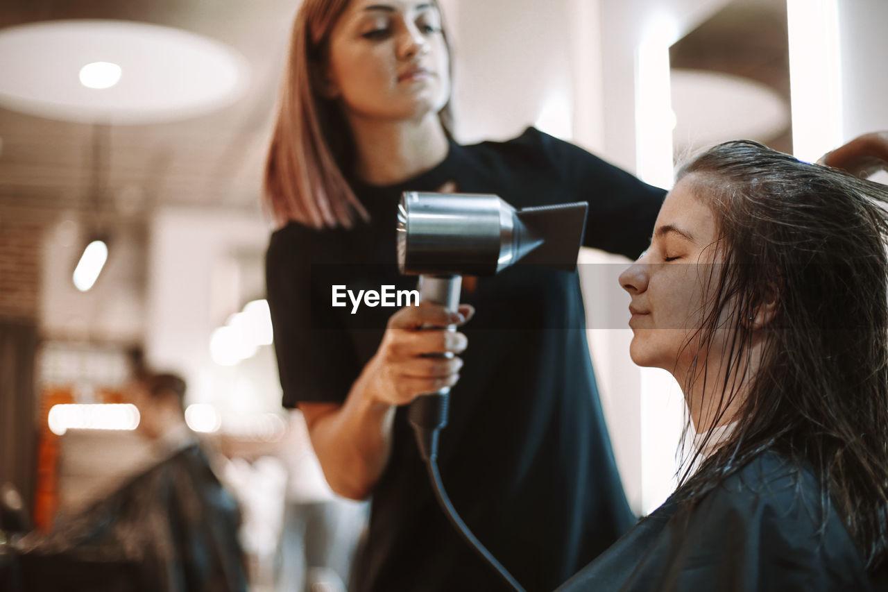 Hairdresser drying hair of customer at salon