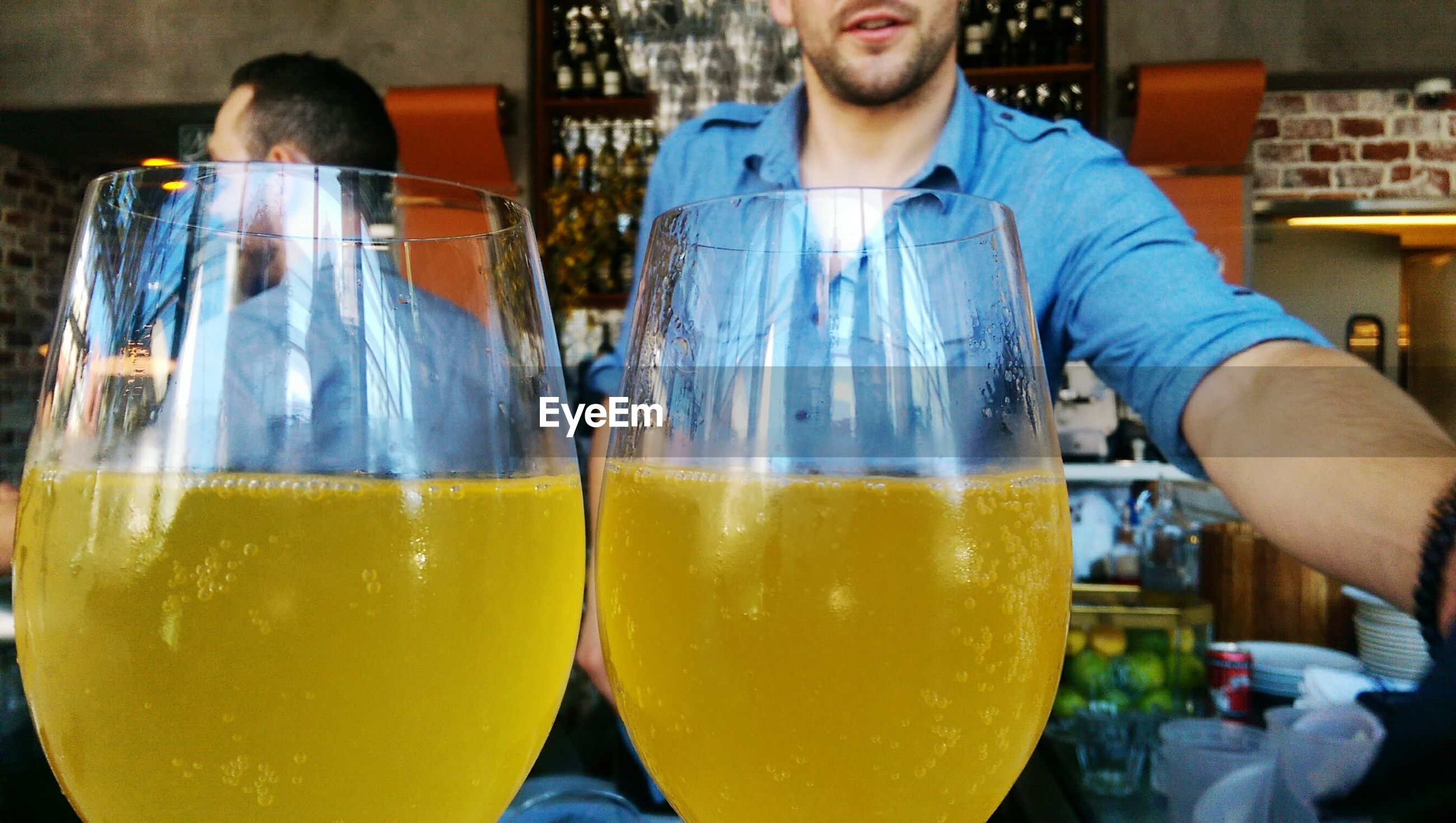 food and drink, glass - material, refreshment, drink, drinking glass, standing, transparent, leisure activity, freshness, focus on foreground, casual clothing, well-dressed