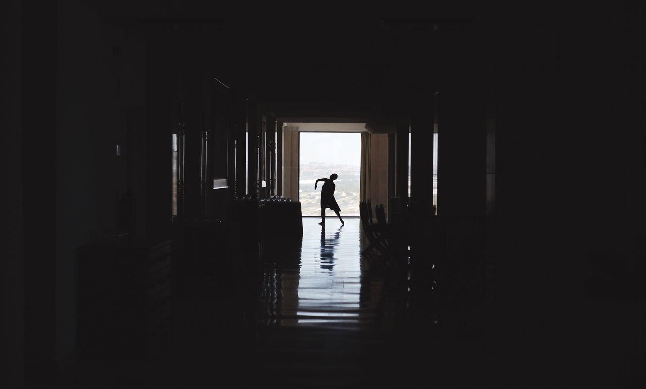 Silhouette Of Person Dancing In Corridor