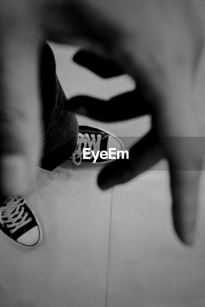 one person, human body part, low section, real people, shoe, body part, human leg, human hand, lifestyles, leisure activity, indoors, women, selective focus, hand, high angle view, fashion, canvas shoe, text, close-up, finger, nail, human limb, human foot