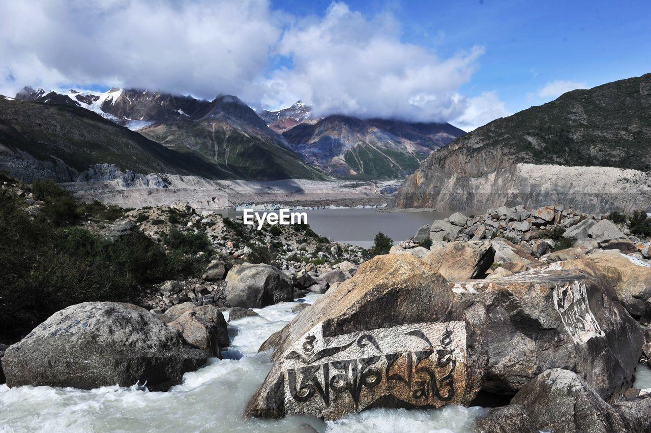 River Flowing Amidst Rocks Against Sky