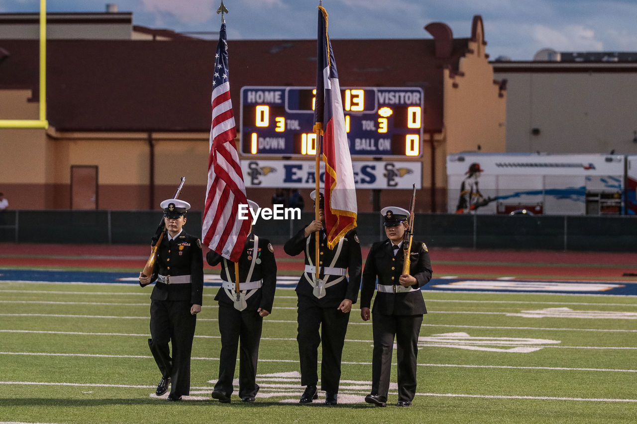 group of people, real people, flag, people, architecture, men, full length, building exterior, patriotism, built structure, sport, adult, focus on foreground, day, lifestyles, togetherness, women, standing, holding, uniform