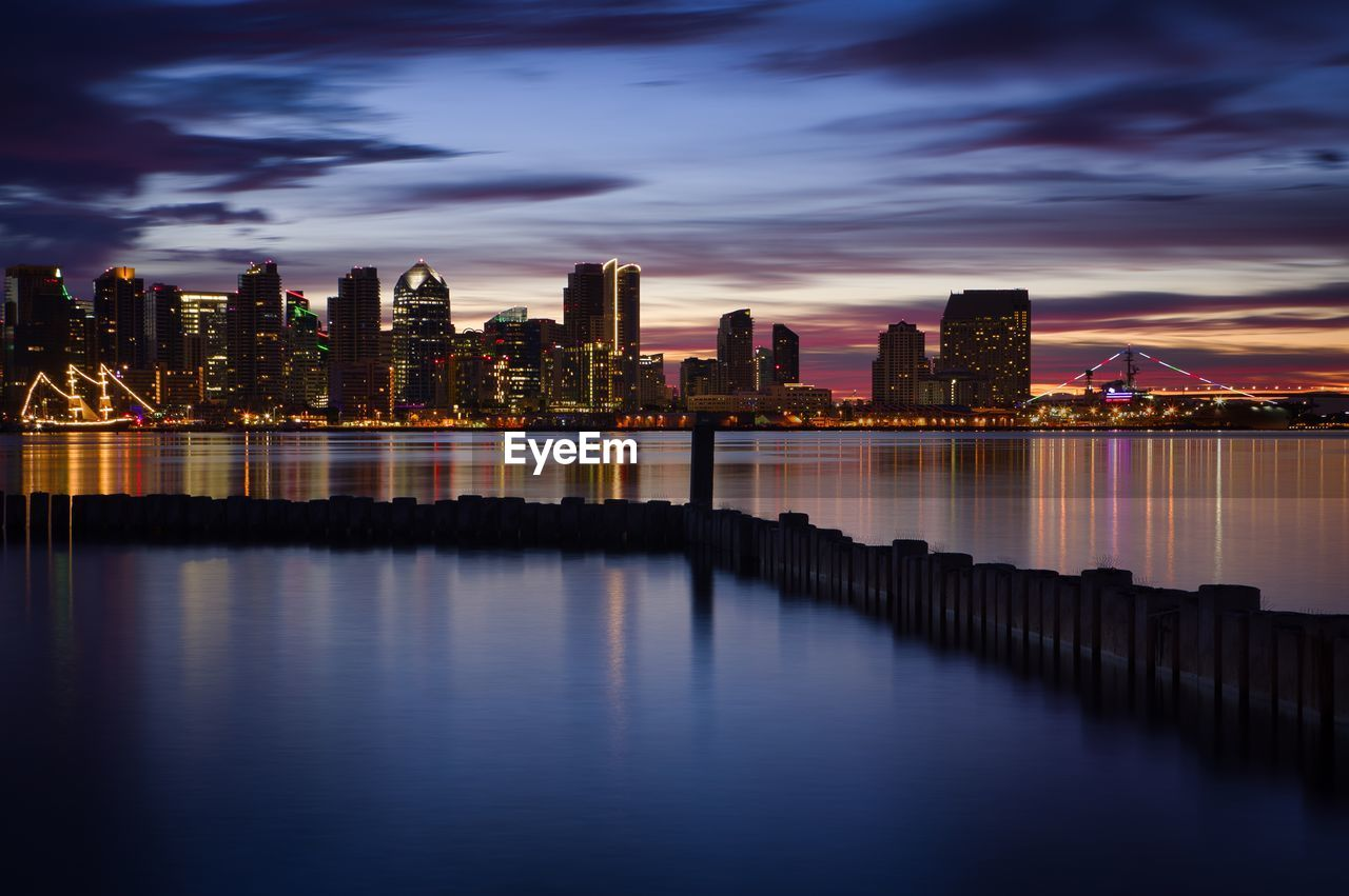 architecture, building exterior, built structure, city, water, sky, building, urban skyline, landscape, waterfront, office building exterior, cloud - sky, skyscraper, illuminated, modern, nature, reflection, no people, cityscape, tall - high, outdoors, financial district