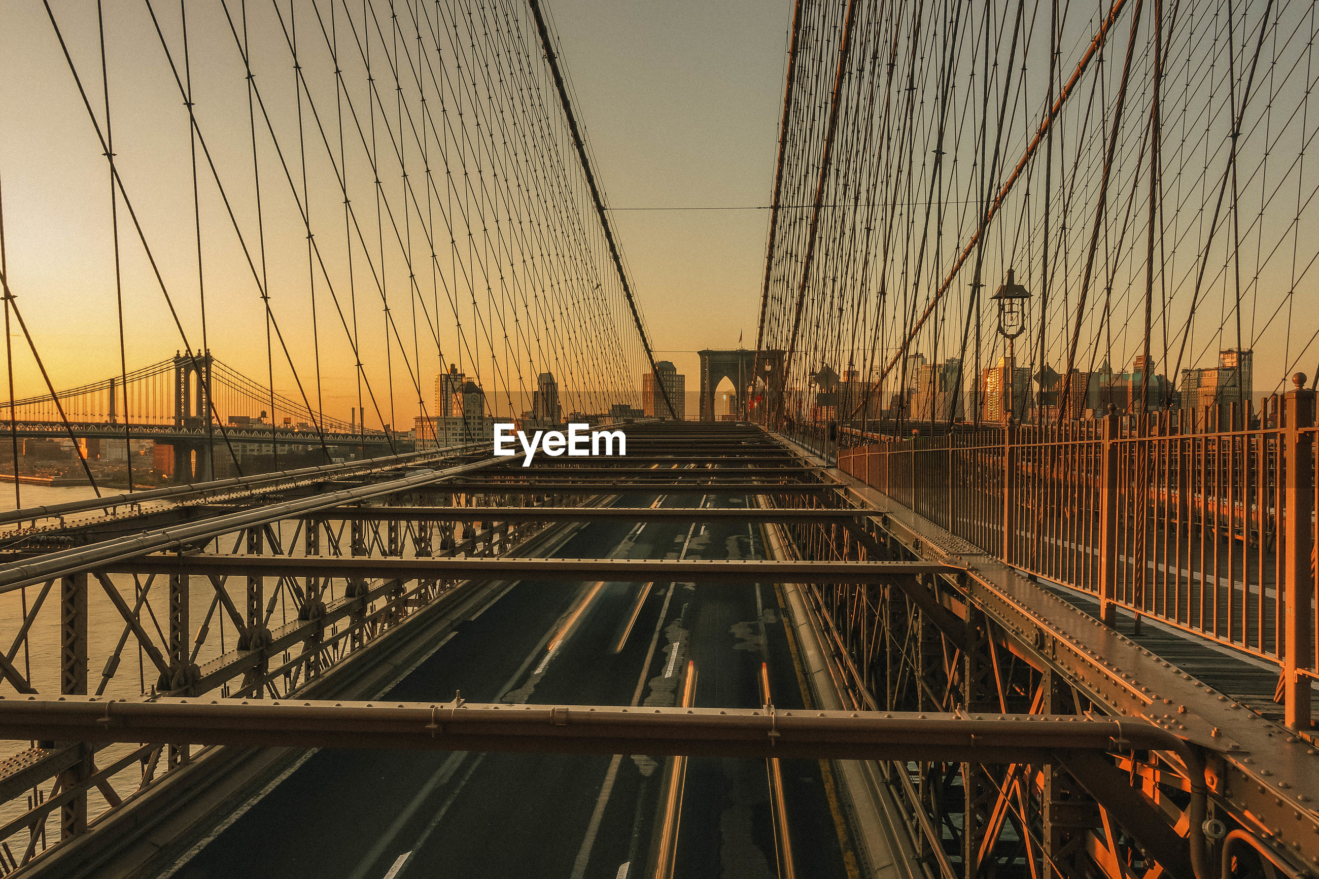 Suspension bridge against sky during sunset