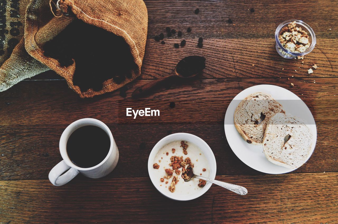 food and drink, drink, refreshment, table, food, cup, mug, freshness, coffee, coffee cup, coffee - drink, wood - material, kitchen utensil, eating utensil, spoon, indoors, directly above, breakfast, still life, high angle view, meal, no people, tea cup, crockery, snack