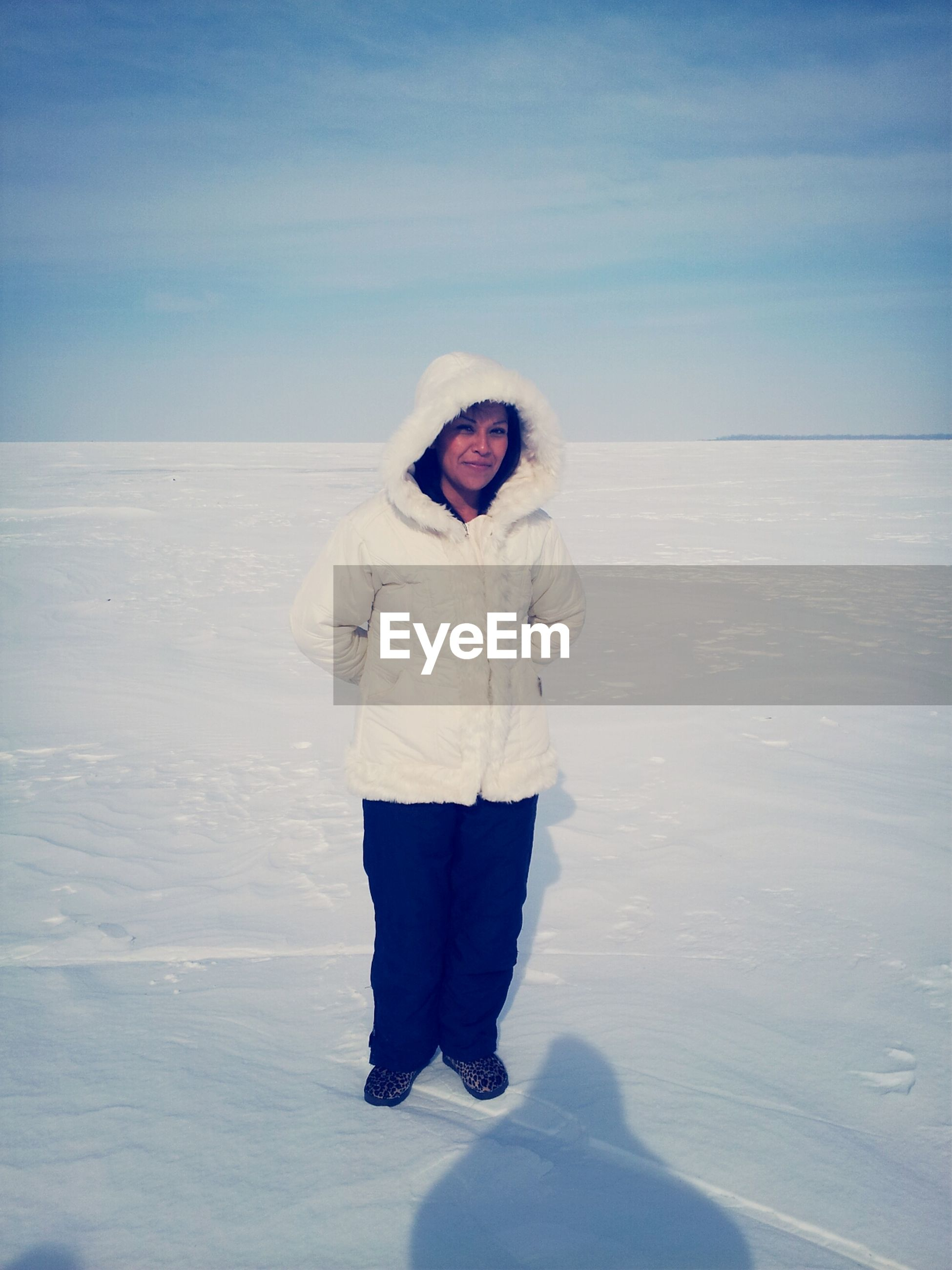 snow, winter, lifestyles, cold temperature, leisure activity, standing, casual clothing, white color, season, young adult, beach, rear view, tranquility, tranquil scene, warm clothing, nature, full length, sky