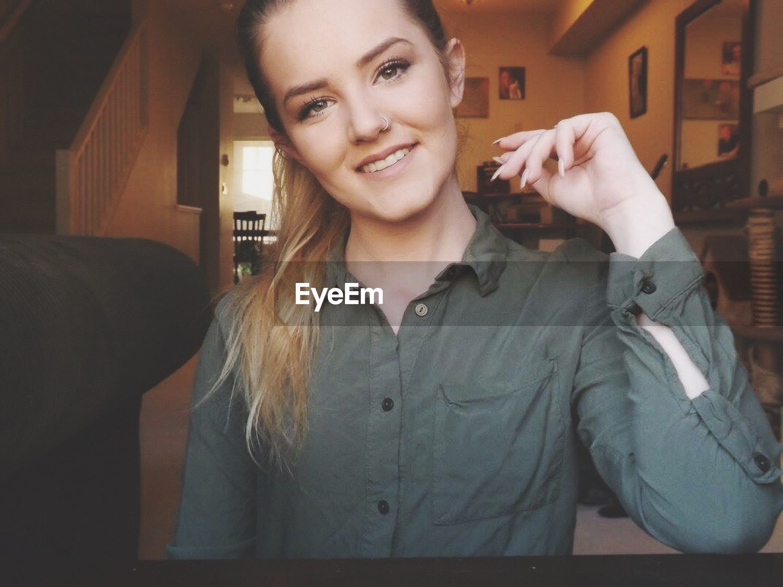 indoors, young adult, lifestyles, person, young women, front view, casual clothing, leisure activity, looking at camera, portrait, standing, home interior, sitting, three quarter length, technology, waist up, smiling