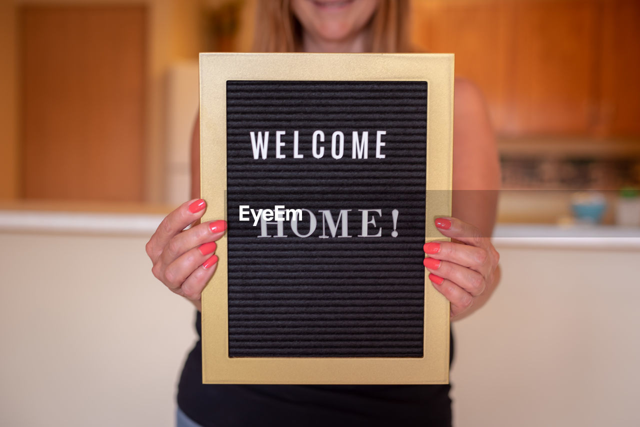 Midsection of woman holding sign at home