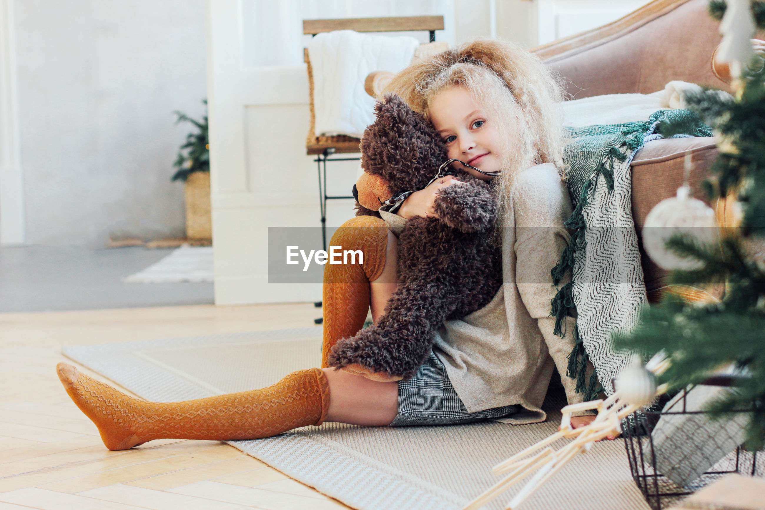 Portrait of girl sitting with toy at home