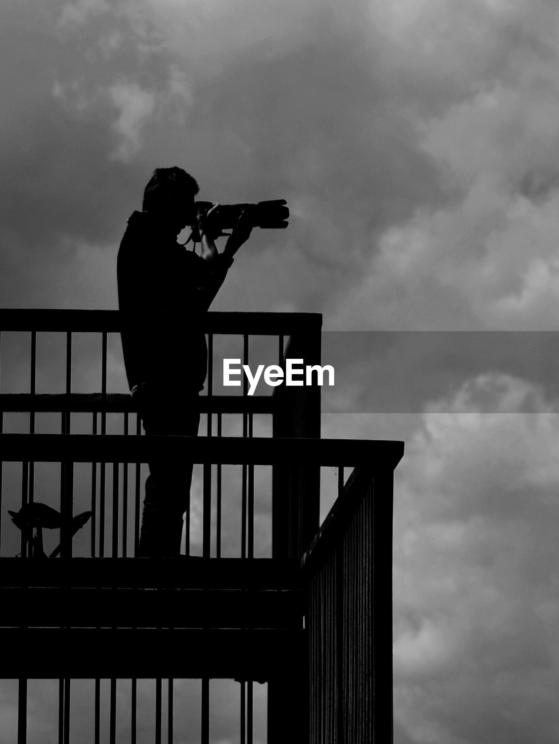 Silhouette of man photographing while standing on balcony