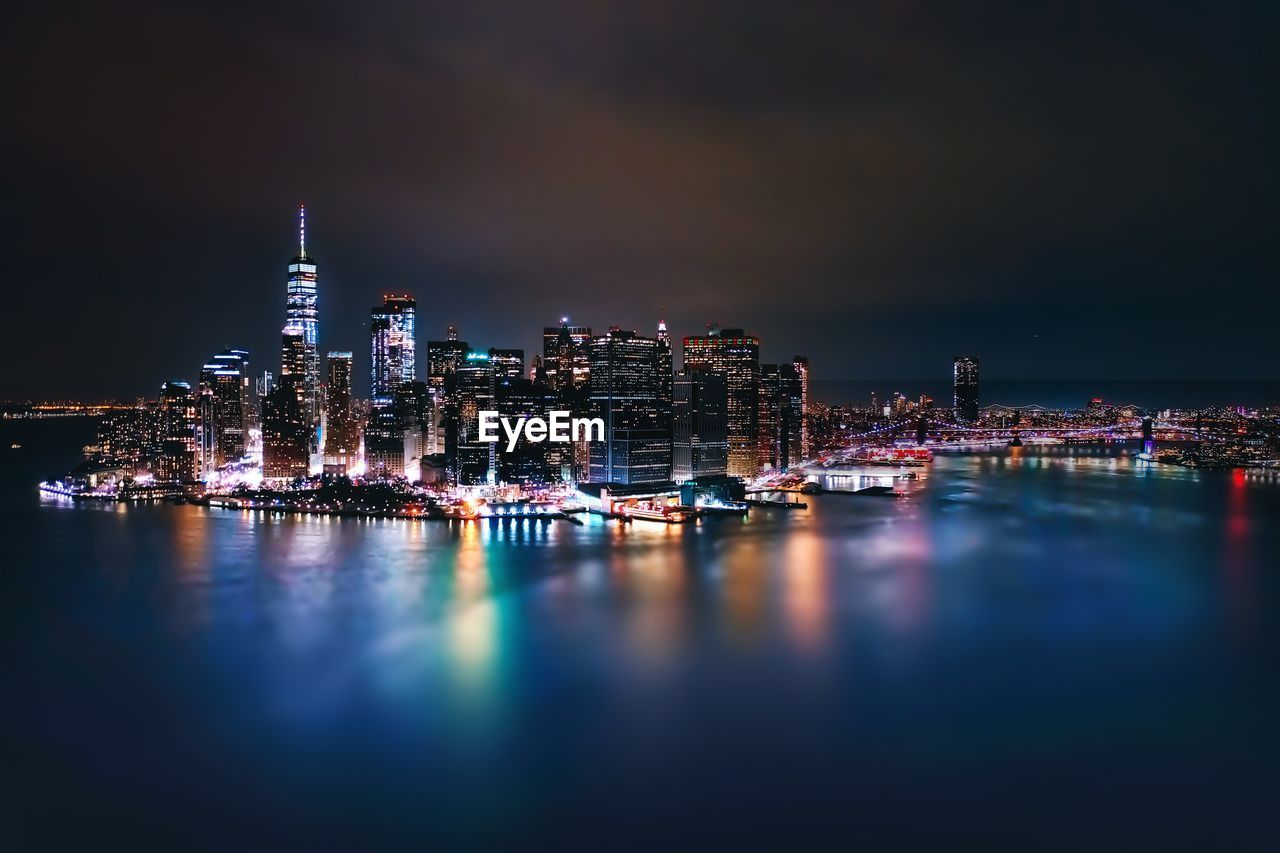 building exterior, architecture, illuminated, city, water, built structure, building, night, waterfront, sky, skyscraper, office building exterior, reflection, cityscape, modern, no people, nature, tall - high, urban skyline, outdoors, financial district, nightlife, spire