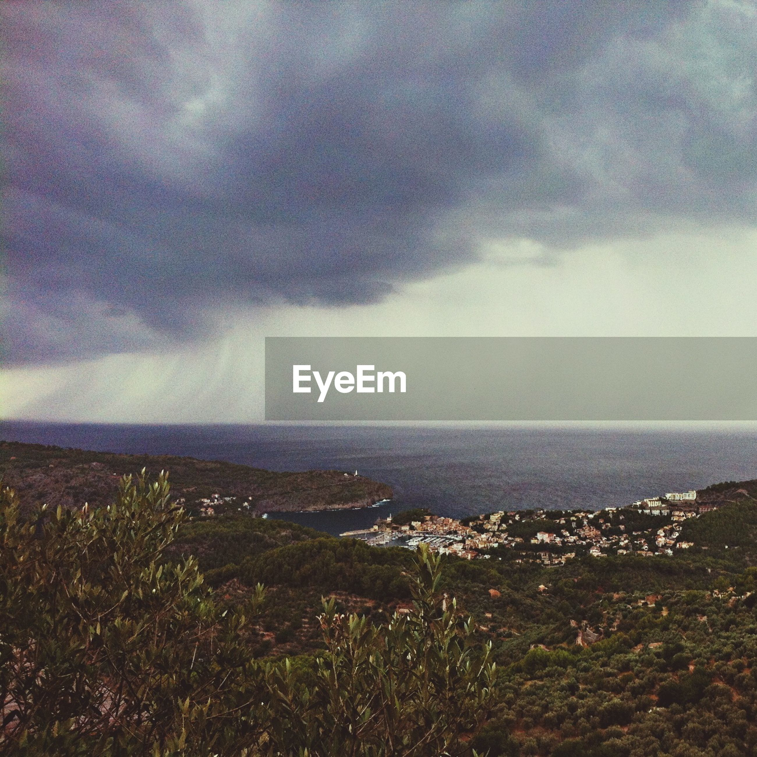 High angle view of landscape by sea against cloudy sky