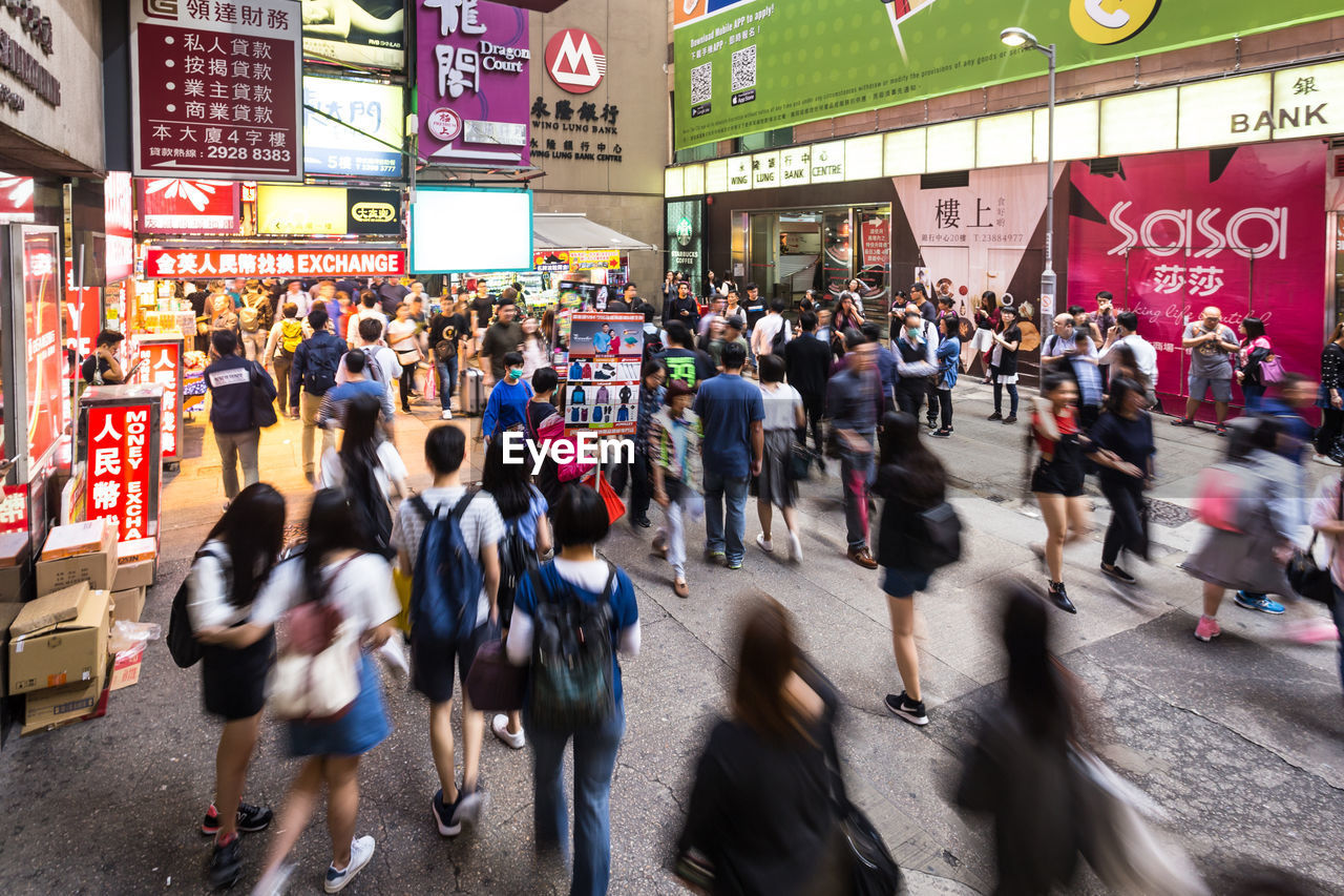 GROUP OF PEOPLE WALKING ON CITY STREET IN MARKET