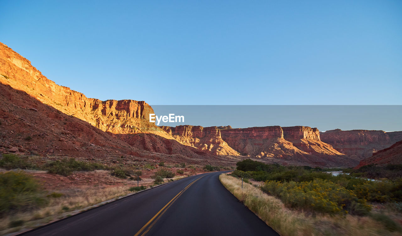 road, rock, rock - object, rock formation, scenics - nature, solid, sky, mountain, transportation, non-urban scene, beauty in nature, nature, the way forward, tranquil scene, no people, direction, tranquility, day, clear sky, symbol, mountain range, diminishing perspective, formation, outdoors, eroded, climate