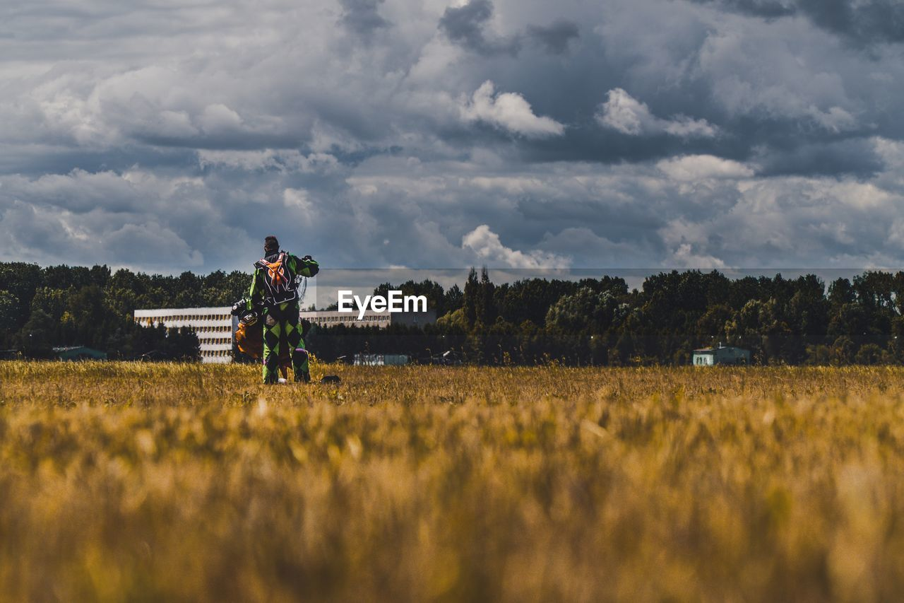 Rear View Of Man Working On Field Against Sky