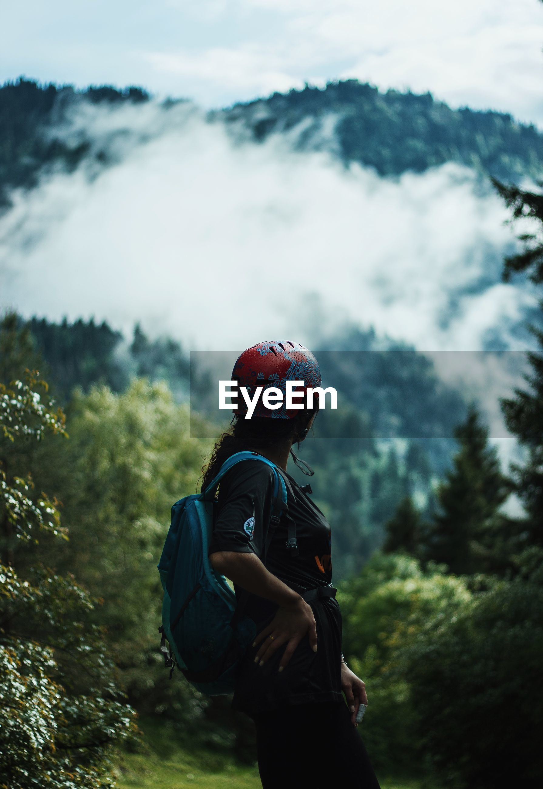 Side view of woman standing while looking at mountain