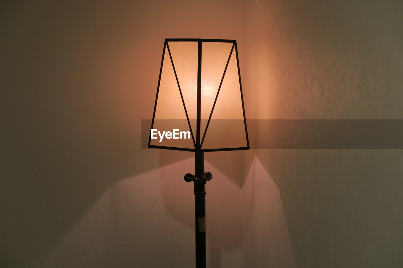 illuminated, lighting equipment, electric lamp, electric light, no people, wall - building feature, indoors, electricity, light, light - natural phenomenon, technology, glowing, home interior, fuel and power generation, lamp shade, orange color, shape, copy space, architecture, light fixture