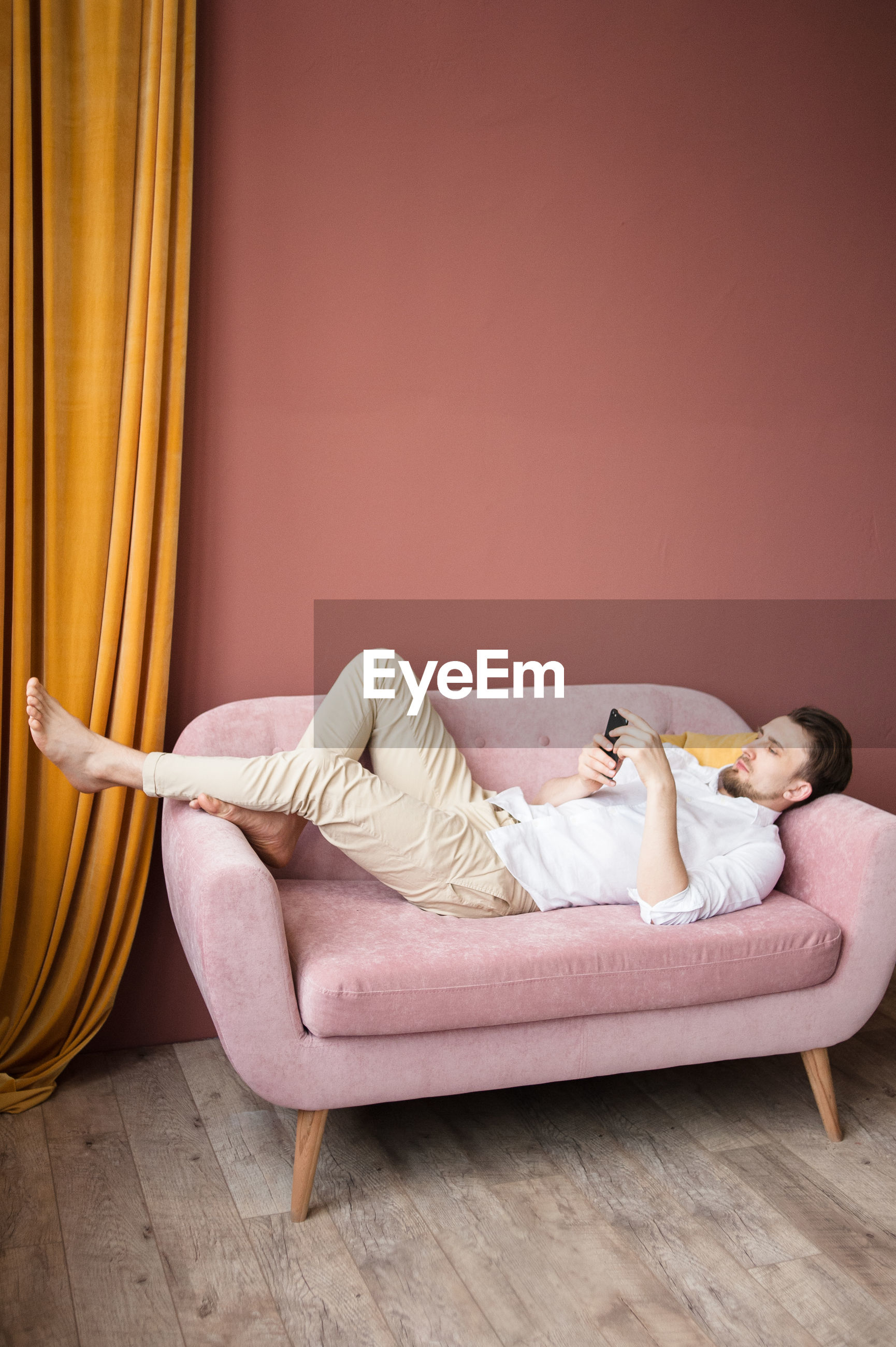 WOMAN LYING ON FLOOR AGAINST WALL AT HOME