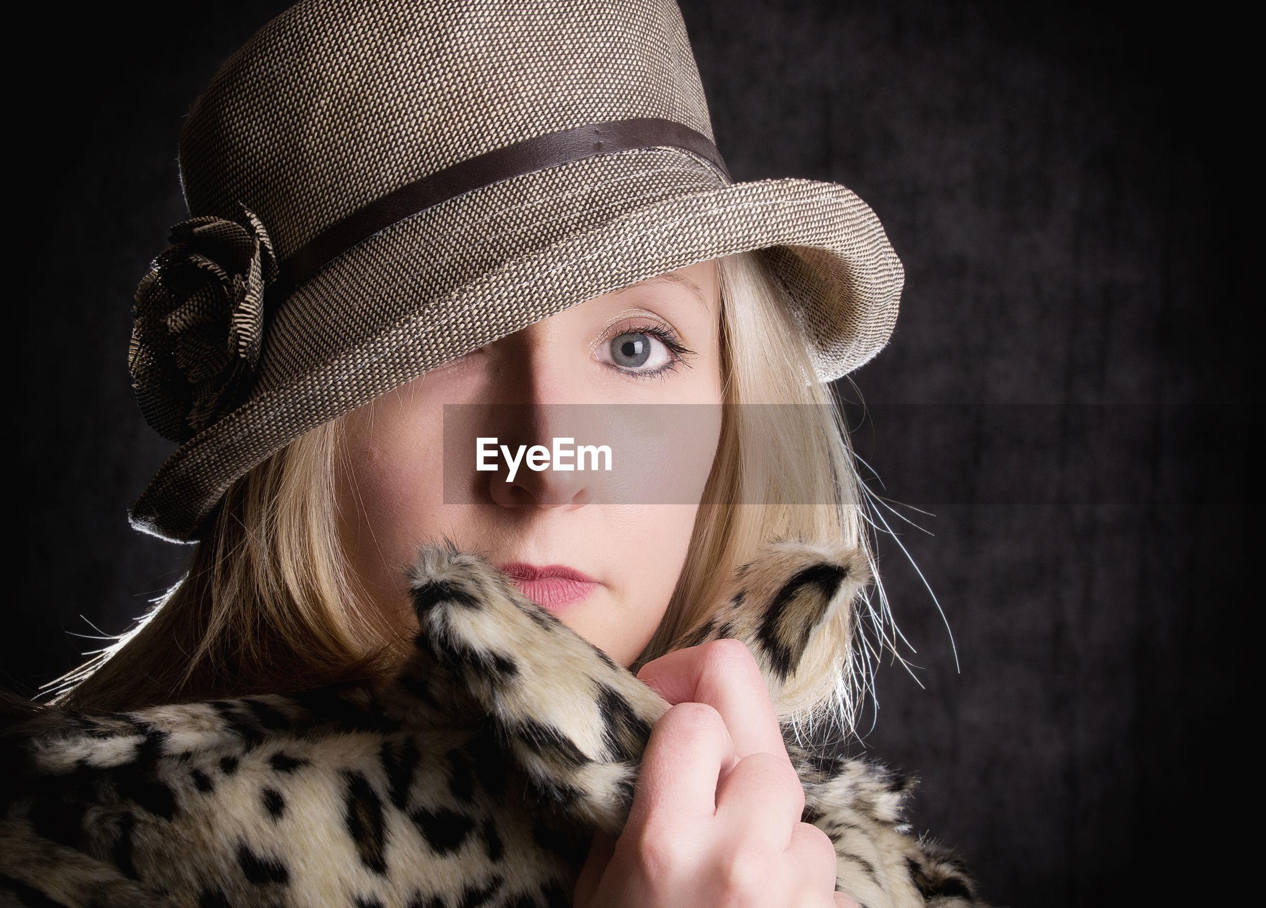 Close-up portrait of beautiful woman wearing hat in dark